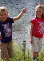 two smiling girls, one holding fish