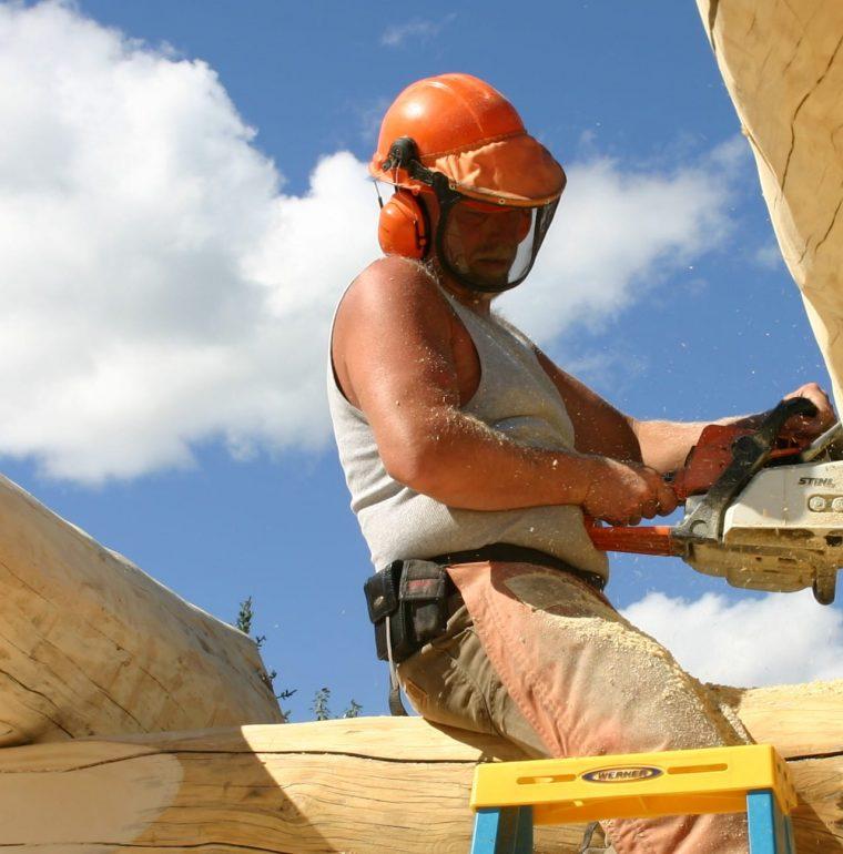 man building log cabin