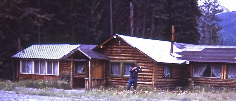 man holding rifle near log cabin