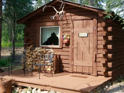 Bear's Den log cabin with chairs and plenty of wood outside