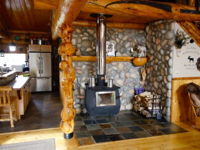 Fireplace surrounded by stone in cabin with kitchen and sitting room