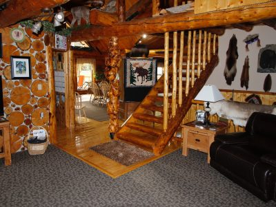Interior view of cabin with wood stairs leading up from sitting room