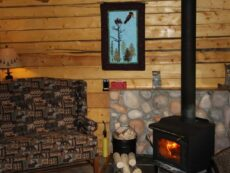 Woodburning stove in Eagle's Nest cabin with comfy chair for relaxing by fire