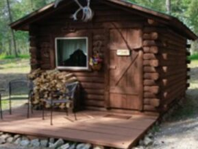 Exterior view of The Duke cabin with 2 chairs on porch and plenty of stacked wood