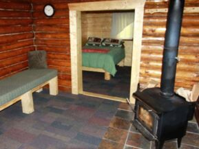 Woodburning stove and seating in Grub Steak Cabin with bedroom beyond
