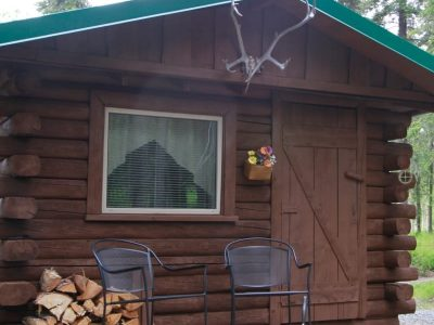 Exterior view of Grub Steak cabin with two chairs for relaxing on porch