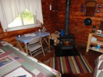 Wood stove and corners of bed in Bear's Den Cabin