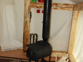 Wood stove in glamping cabin with bucket of wood nearby