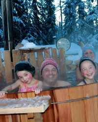 Family in hot tub surrounded by snow