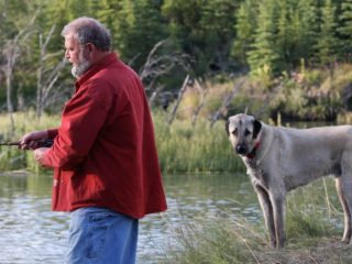 Man fishing with dog nearby