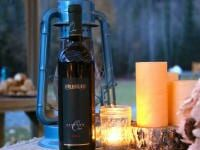 Bottle of wine near candles and lantern