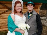 Bride and groom in front of cabin