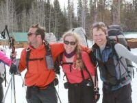 3 people taking a break from skiing to smile at camera