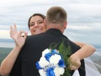 bride with blue and white bouquet making ok sign with hands while hugging groom
